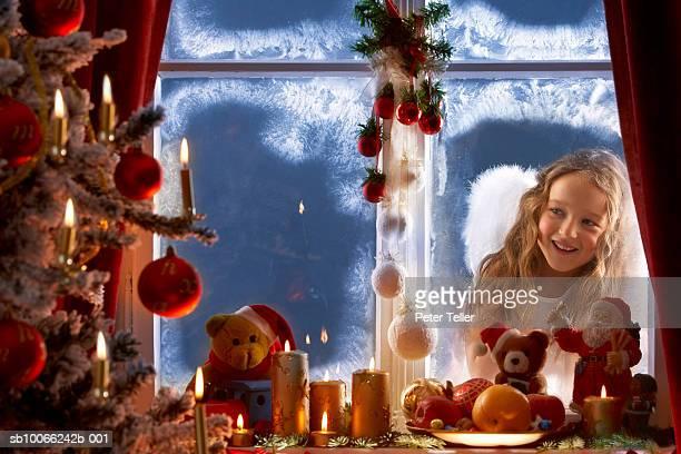 girl (5-6) wearing angel wings peering through window into house - christkind stock-fotos und bilder