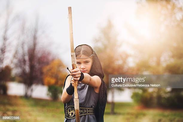 Girl wearing archer costumes holding bow and arrow looking at camera
