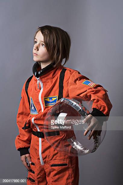 Girl (7-9) wearing astronaut costume, looking up