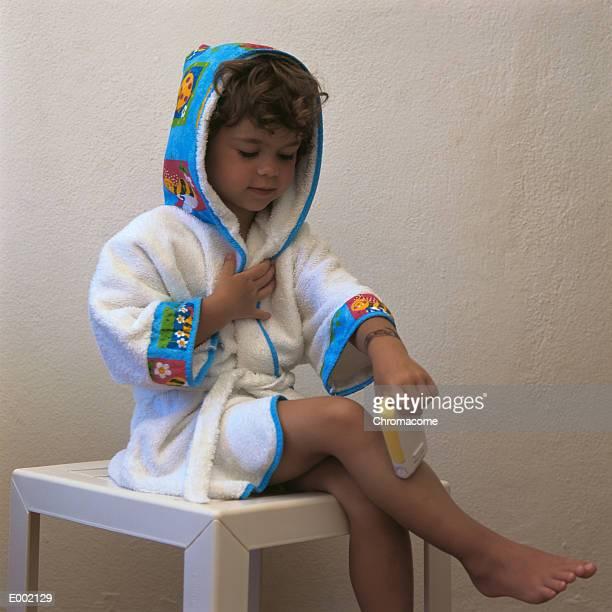 Girl wearing bathrobe, sitting on table, pretending to shave legs