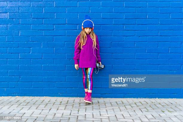 girl wearing blue cap and oversized pink pullover standing in front of blue wall listening music with headphones - digital native stock pictures, royalty-free photos & images