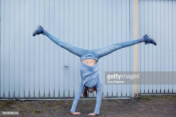 girl (10-11) wearing blue clothes and doing a cartwheel in front of blue garage doors - blue shoe stock pictures, royalty-free photos & images