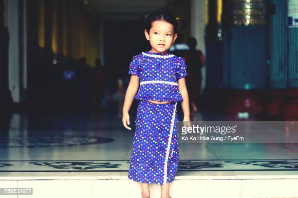 girl wearing blue dress looking away while standing at lobby - ko ko htike aung stock pictures, royalty-free photos & images