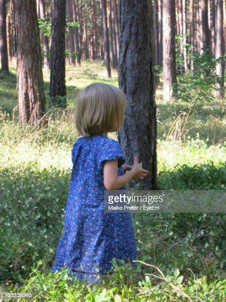 Girl Wearing Blue Floral Dress Standing Amidst Plants In Forest