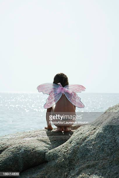 girl wearing butterfly costume, crouching on rock and looking at ocean - bikini bottom stock pictures, royalty-free photos & images