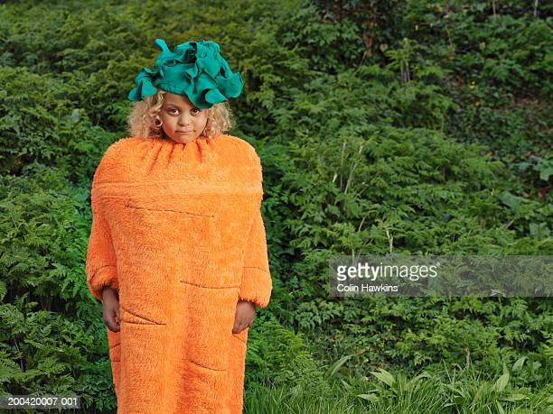Girl (5-7) wearing carrot costume outdoors, portrait