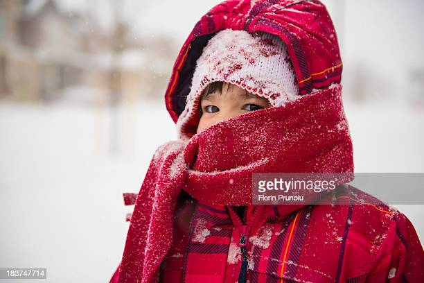 Girl wearing coat, scarf and hat with hood