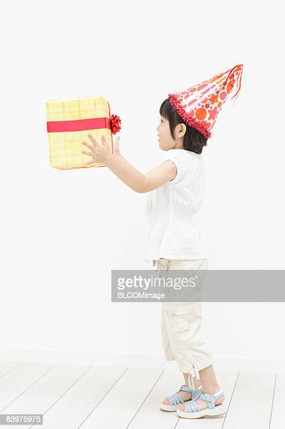 Girl wearing cone hat holding present box, side view