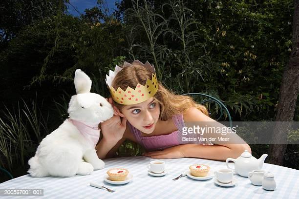 girl (10-11) wearing crown having tea party with toy rabbit - conto de fadas - fotografias e filmes do acervo