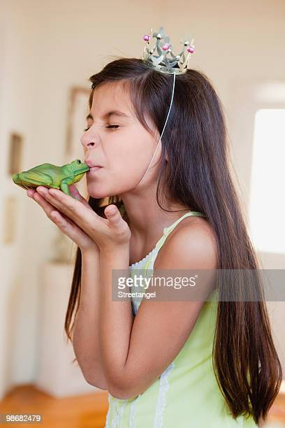 girl wearing crown kissing toy frog