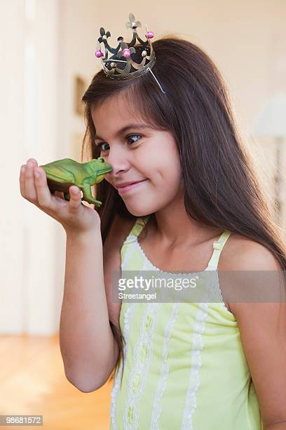 girl wearing crown playing with toy frog