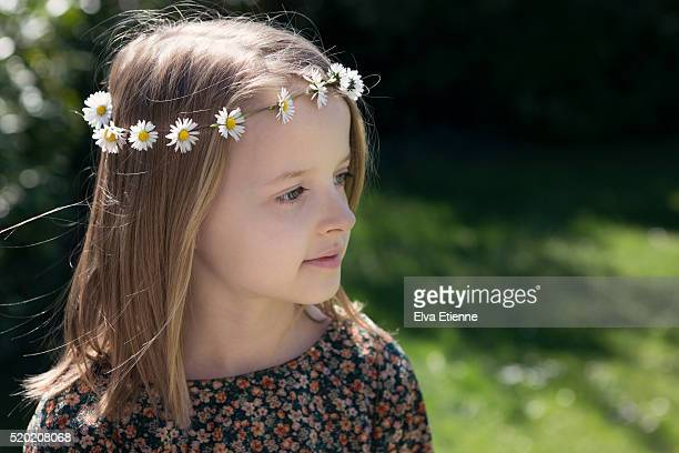 Girl (9-10) wearing daisy chain headband