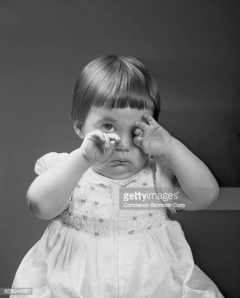 Girl wearing dress with hands covering eyes one eye open looking sad Not happy with new haircut