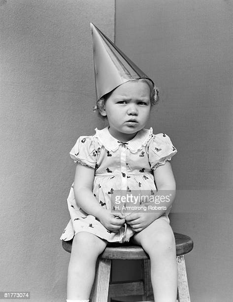 Girl Wearing Dunce Cap Sitting On Stool In Corner Unhappy Punishment Angry.