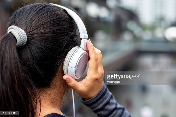 girl wearing earphone,listening music in downtown