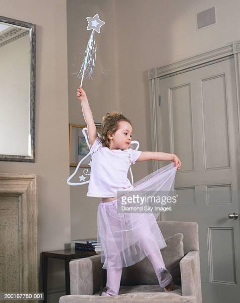 Girl (3-5) wearing fairy costume, arm raised, holding wand