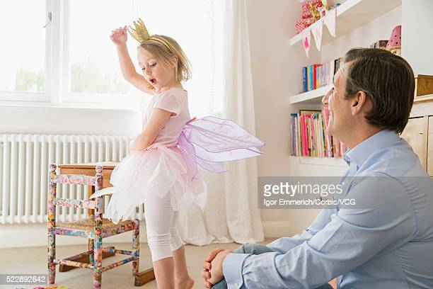 Girl (4-5) wearing fairy costume dancing in front of father