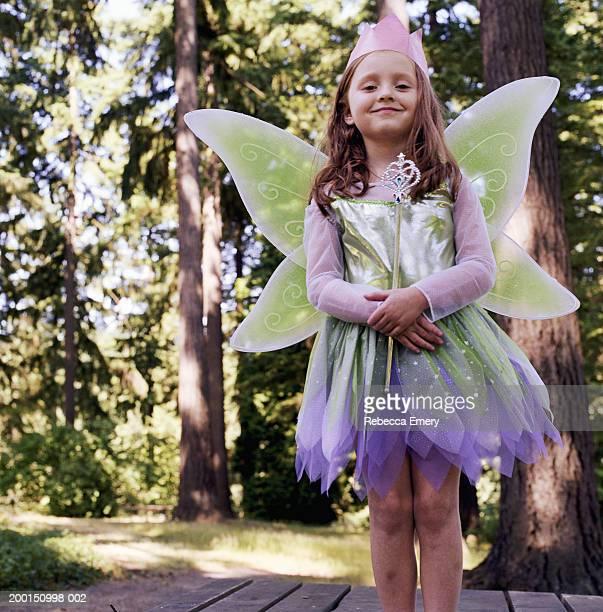 Girl (4-6) wearing fairy costume, holding wand, portrait