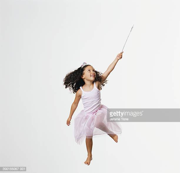 Girl (3-5) wearing fairy costume jumping, holding wand