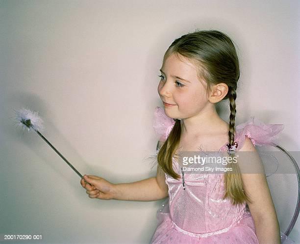 Girl (4-6) wearing fairy costume, waving wand, smiling
