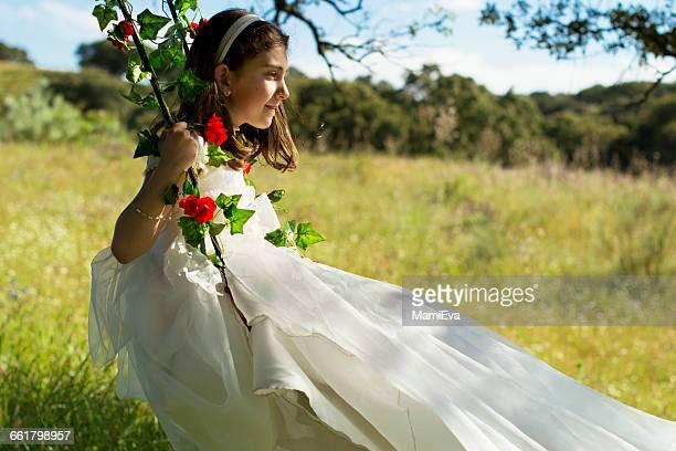 Girl wearing first communion  dress sitting on swing in field