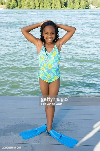 Girl (10-12) wearing flippers on dock, hands behind head, portrait
