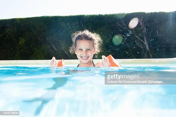 Girl wearing floatie in swimming pool