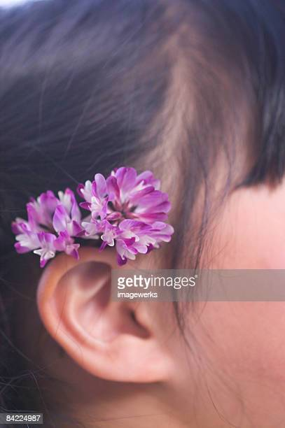 Girl (6-7) wearing flowers behind ears, close-up