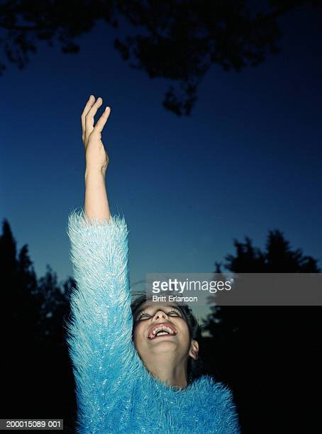 Girl (9-11) wearing fluffy jumper reaching towards sky, laughing