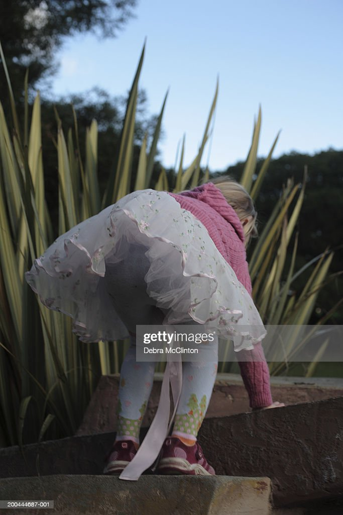 Girl (4-6) wearing frilly skirt and pink sweater climbing up steps : Stock Photo