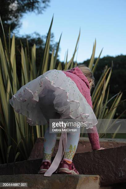 girl (4-6) wearing frilly skirt and pink sweater climbing up steps - little girls dressed up wearing pantyhose stock photos and pictures