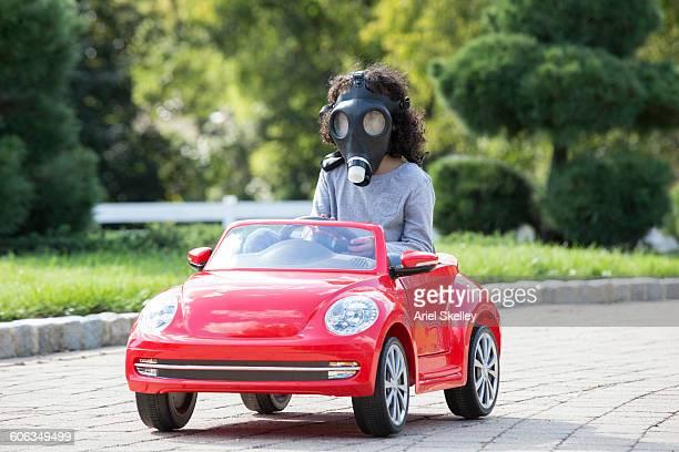 Girl wearing gas mask driving toy car