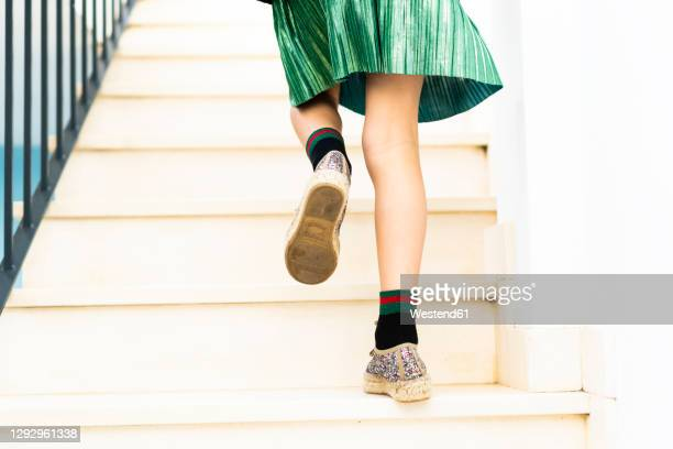 girl wearing green skirt running upstairs - green skirt stock pictures, royalty-free photos & images