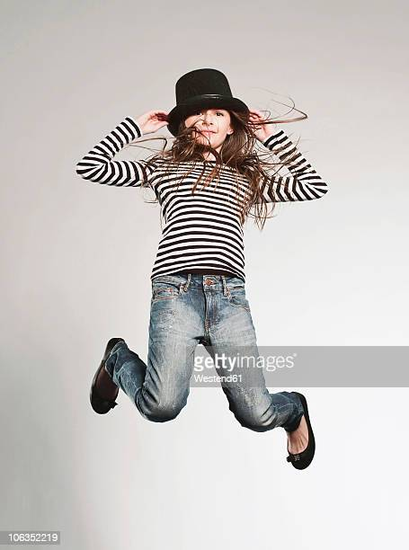 Girl (8-9) wearing hat and jumping, smiling, portrait