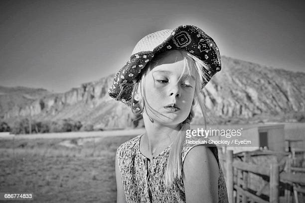 Girl Wearing Hat While Looking Down Against Mountains