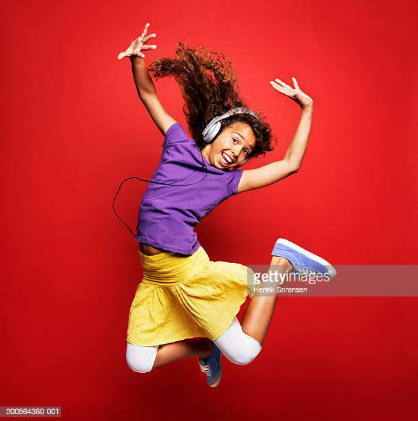Girl (12-13) wearing headphones and jumping, smiling, portrait