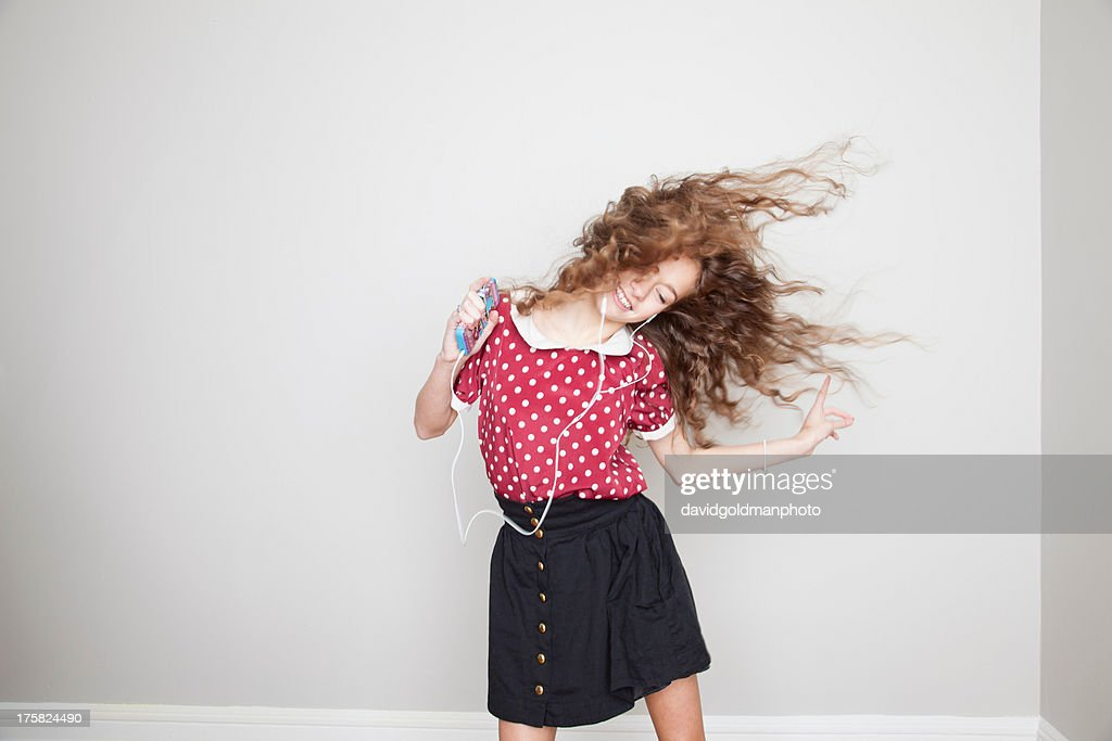 Girl wearing headphones, dancing and holding mp3 player : Stock Photo