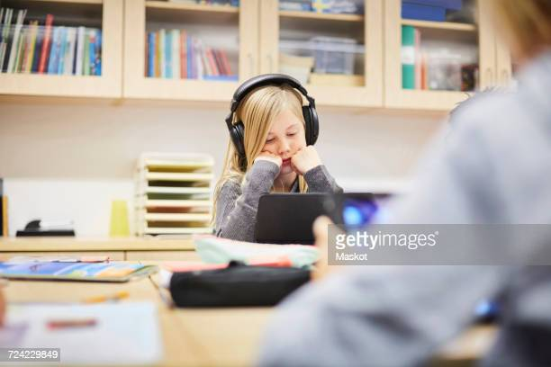 Girl wearing headphones while looking at digital tablet at desk in classroom