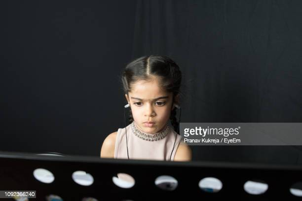 Girl Wearing Hearing Aid While Reading Against Wall