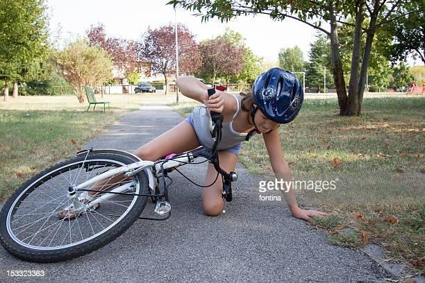 Girl wearing helmet and fallen with her bike