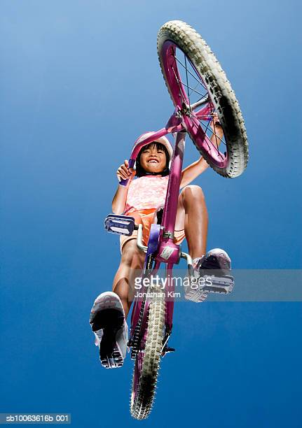 girl (4-5) wearing helmet, riding bicycle, low angle view - low angle view stock pictures, royalty-free photos & images