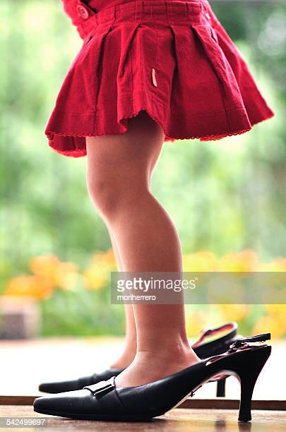 Girl wearing her mother's high heel shoes