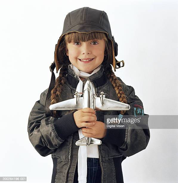 Girl (3-5) wearing hood holding toy aeroplane, smiling, portrait