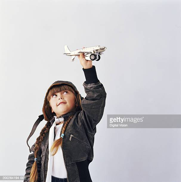 Girl (3-5) wearing hood holding up toy aeroplane