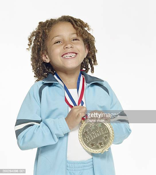 Girl (4-6) wearing large gold medal, smiling