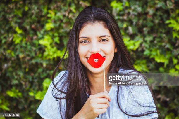 Girl wearing lipstick prop on her face.