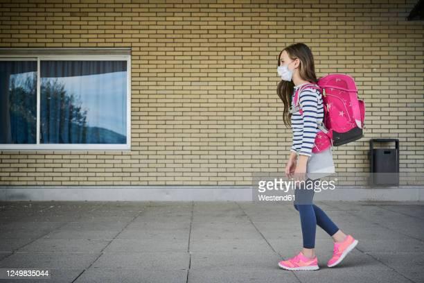 girl wearing mask and schoolbag walking along building - schulkind nur mädchen stock-fotos und bilder