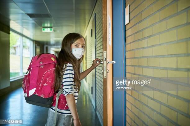 girl wearing mask in school opening classroom door - bildung stock-fotos und bilder