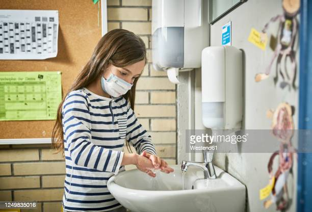 girl wearing mask in school washing her hands - education stock pictures, royalty-free photos & images