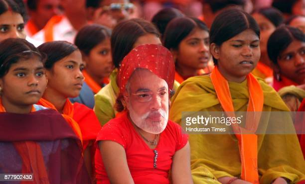 A girl wearing masked of Modi during an election rally of Gujrat Chief Minister Narender Modi at Ahwa in district Dangs in South Gujarat 400Kms from...